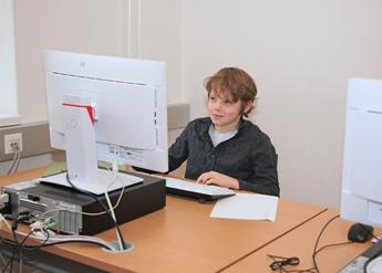 Das Bild zeigt einen Schüler der vor einem Computer sitzt
